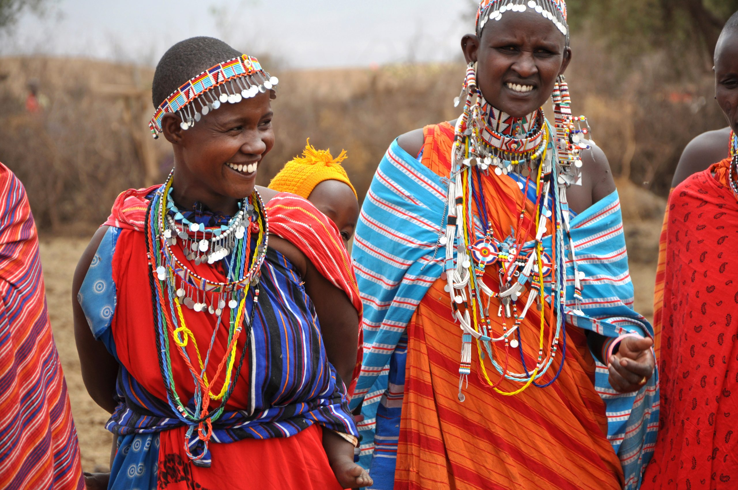 Amboseli National Park, Kenya - September, 2014: Portarait of group of african women with traditional colorful ornaments (necklace, earrings) smiling and greeting tourists with traditional jumping dance