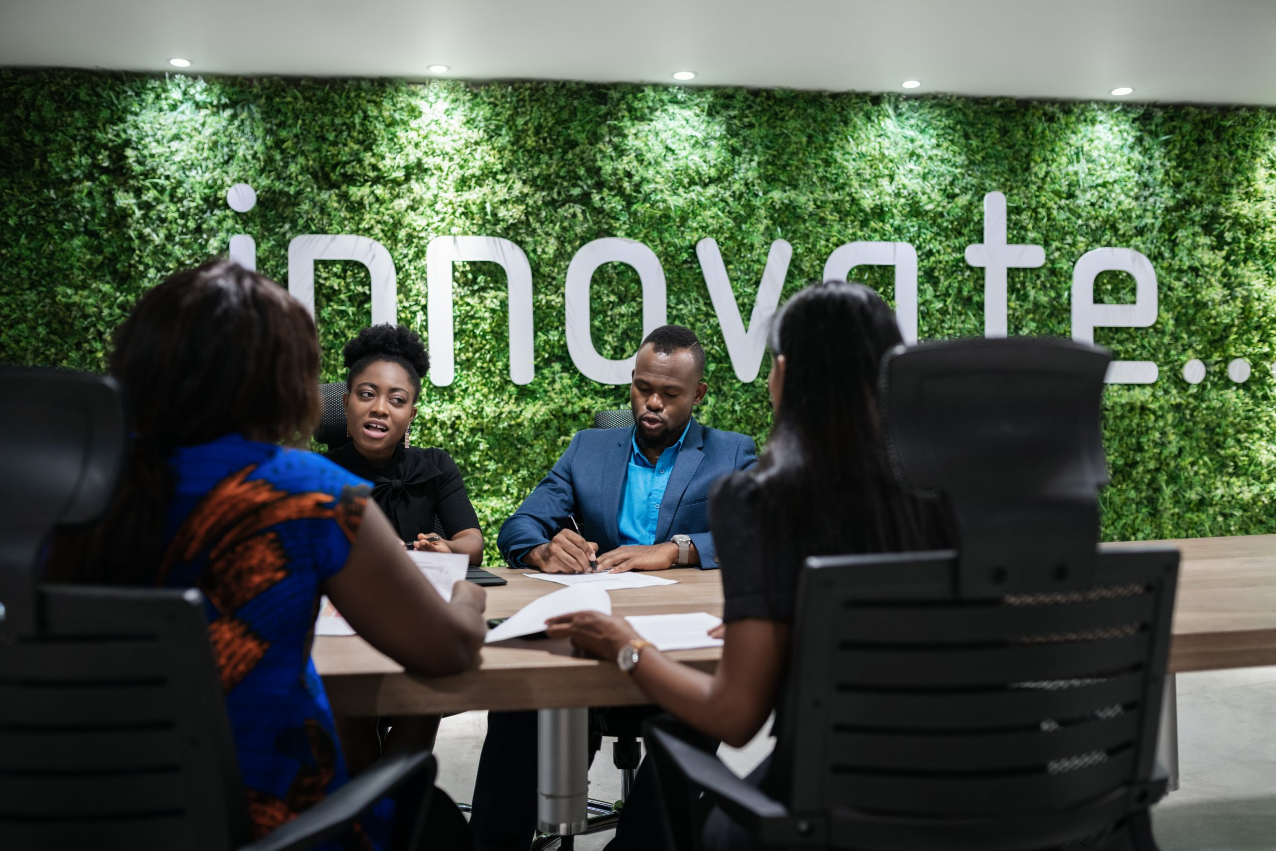 Young African businesswoman discussing work with a group of colleagues during a meeting around a boardroom table in an office